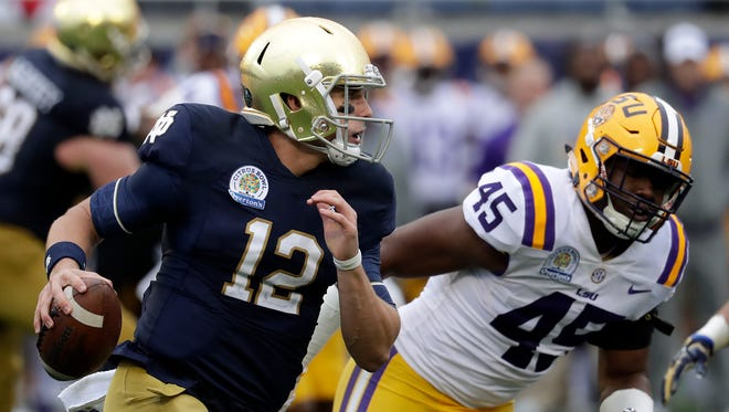 Notre Dame quarterback Ian Book (12) shambles for yardage past LSU linebacker Michael Divinity Jr. (45) during the first half of the Citrus Bowl  on Monday in Orlando, Fla.