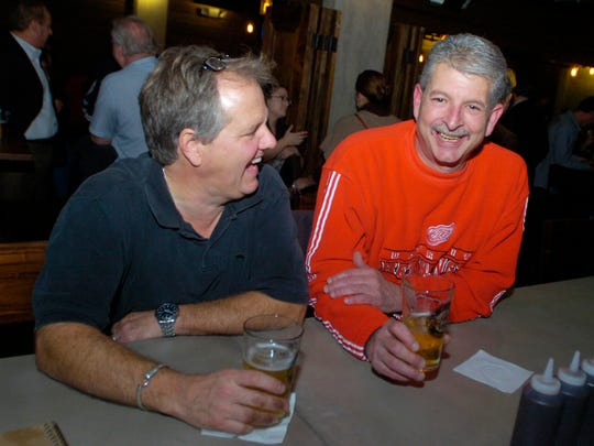 Brian Sarver from Beverly Hills, left, and Gary Petrovski from Royal Oak enjoy a beer at the now open lower level at Lockhart's BBQ in Royal Oak.