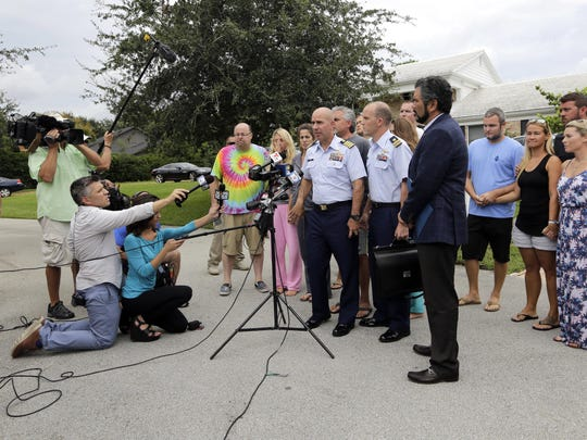 Mark Fedor, chief of response for the U.S. Coast Guard 7th District, center, makes a statement outside of the homes of the two teenagers missing since a fishing trip last Friday, Wednesday, July 29, 2015, in Tequesta, Fla.  The Coast Guard announced that the search for Nick Cohen and Austin Stephanos continues.