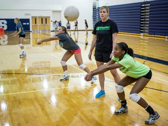 Senior Mya Rhodes bumps the ball as coach Randi Jakubiak watches during volleyball practice Thursday, August 11, 2016 at Marysville High School.