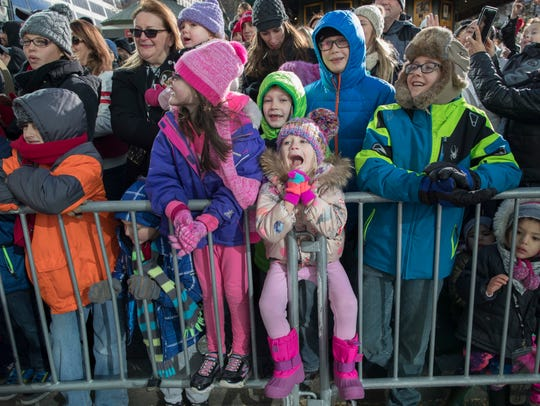 Children watch as the balloons float down Avenue of