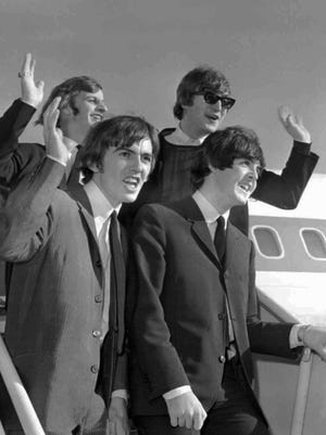 The Beatles wave after arriving in San Francisco Aug. 18, 1964, to begin an American tour.