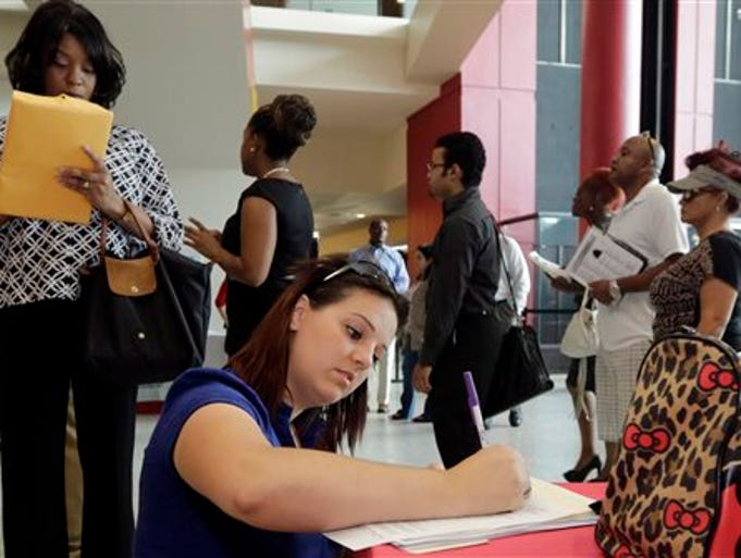 In this photo taken Tuesday, Aug. 19, 2014, Jessica Pimentel, of Hollywood, Fla., fills out a job application during a job fair in Sunrise. Fla.  The Labor Department says applications for jobless aid rose 4,000 to a seasonally adjusted 302,000. The four-week average, a less volatile measure, increased 3,000 to a still-low 299,750. A steady decline over the summer in applications means that 2.46 million people collected benefits last week, the lowest total since June 2007, a few months before the Great Recession began.