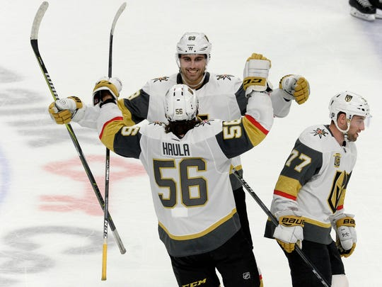 Vegas Golden Knights left wing Erik Haula (56) celebrates his game-winning goal with right wing Alex Tuch, facing, and defenseman Brad Hunt (77) following a shootout in an NHL hockey game against the Buffalo Sabres, Saturday, March 10, 2018 in Buffalo, N.Y. (AP Photo/Adrian Kraus)