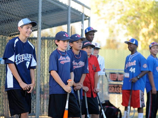 Twelve year olds from Tulare, Los Altos, Utah, Arizona, and Oakland stand in line to participate in a bunting competition during Opening Day at the Tulare Baseball Association Complex on Sunday.