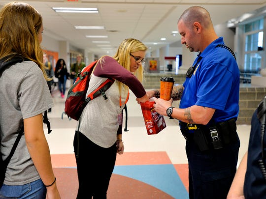 Tony Koutsos, a school resource officer at Mauldin High School, lets a student take one of the doughnuts gifted to him before classes start on Nov. 6, 2015.