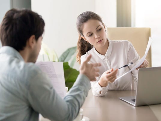 Conversation between businesswoman and businessman about documents at office table