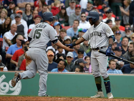 Seattle Mariners' Kyle Seager, left, celebrates with teammate Guillermo Heredia, right, after scoring on a wild pitch by Boston Red Sox's Rick Porcello in the fourth inning of a baseball game, Sunday, May 28, 2017, in Boston. (AP Photo/Steven Senne)