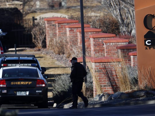 An investigator heads to the scene of shooting Sunday,
