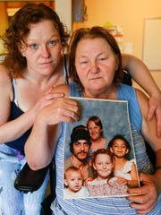 Margaret Montgomery and her daughter Ilene Montgomery hold a family portrait that includes Raquel Montgomery on the right. Raquel was murdered on Tuesday, Feb. 13, 2018.