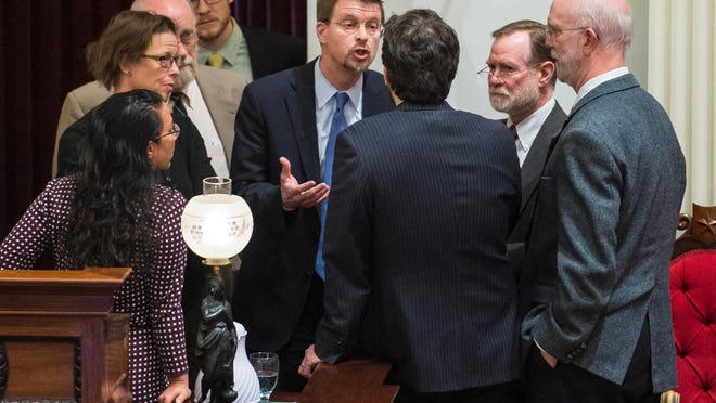 House Speaker Shap Smith, D-Morristown, center,speaks with Rep. Chris Pearson, P-Burlington, back to camera, and other legislators during a break in debate on a bill that would prohibit teachers strikes.