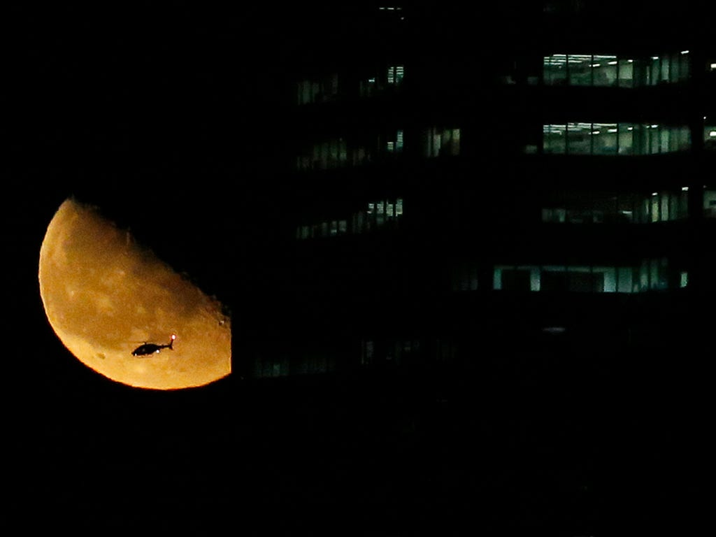 A photo taken from Jersey CIty, N.J., shows a helicopter and rising moon near a building in Manhattan on early March 13.