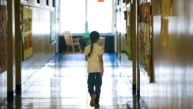 A student walks down the hallway of Casimir Pulaski Elementary School in Wilmington. Mold recently was discovered in three classrooms.