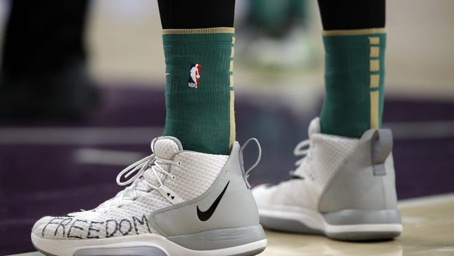 """Boston Celtics' Enes Kanter has the word """"Freedom"""" written on his sneakers during the first half of an NBA basketball game against the Los Angeles Lakers earlier this year."""