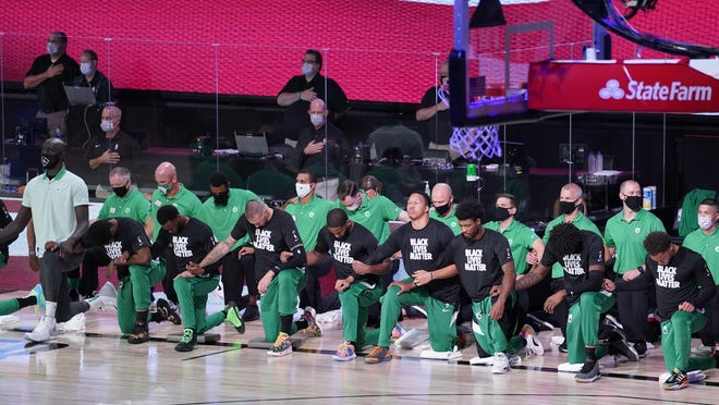 Members of the Boston Celtics kneel during the national anthem prior to an NBA conference semifinal playoff basketball game against the Toronto Raptors, Monday, Sept. 7, 2020, in Lake Buena Vista, Fla.