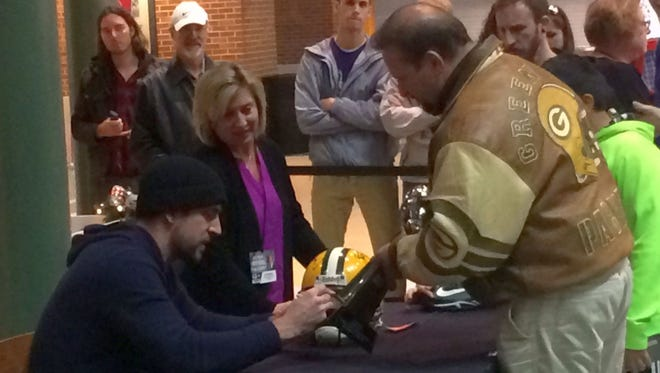 Green Bay Packers quarterback Aaron Rodgers, left, signs helmets and other items for fans in the Lambeau Field Atrium in Green Bay on Monday night, Dec. 12, 2016. Rodgers signed 200 autographs for a minimum donation of $100 each to raise money for The Salvation Army of Greater Green Bay.