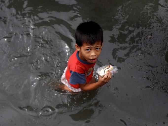 A boy eats a sandwich as he wades along a flooded street on Aug. 21 in Muntinlupa City near Manila.