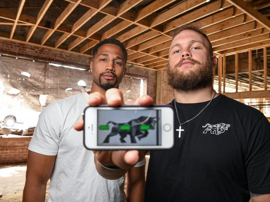 Business partners Ben Boulware, rightt, and Marcus Brown use a cell phone to display the interactive technology that be available at The Junkyard fitness center in downtown Anderson.