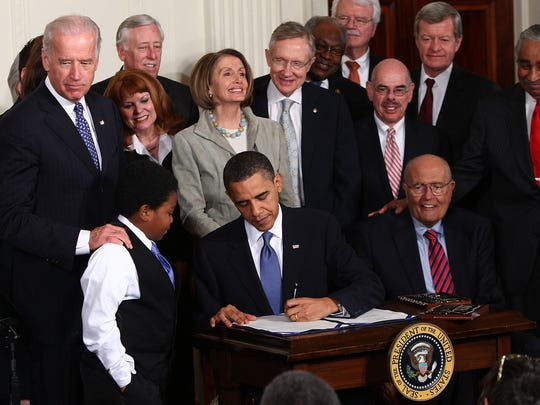 President Barack Obama signs the Affordable Health Care for America Act during a ceremony with fellow Democrats in the East Room of the White House March 23, 2010 in Washington, DC. The historic bill was passed by the House of Representatives Sunday after a 14-month-long political battle that left the legislation without a single Republican vote.  (Photo by Win McNamee/Getty Images) *** Local Caption *** James Clyburn;John Dingell;Harry Reid;Henry Waxman;Nancy Pelosi;Joe Biden;Steny Hoyer;George Miller;Charlie Rangel;Barack Obama