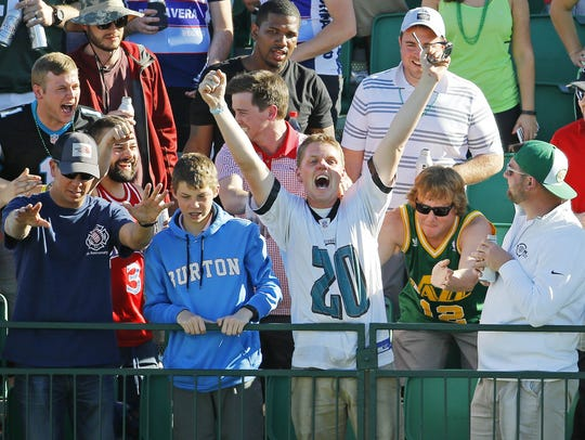 A fan celebrates after catching a ball thrown in the