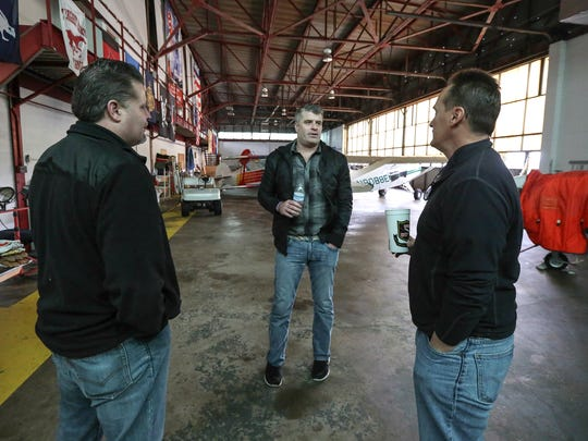 Bart Conley, center, and his brother, Patrick, left check out a hangar at Bowman Field with Jeff Daus, right, where they held a Jill's Wish charity event last year and are making plans to hold it again in 2017.