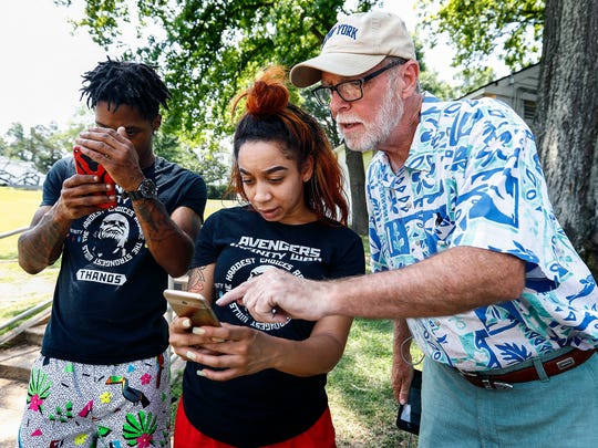 Pokémon Go players (left to right) Brandon Tyler, Natasha Pittman, and Allen Parker collect a pocket monster during a raid at Levitt Shell, Thursday afternoon.