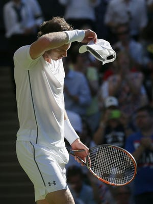 Andy Murray of Britain wipes his face after defeating Mikhail Kukushkin of Kazakhstan in the singles first round match at the All England Lawn Tennis Championships in Wimbledon, London, Tuesday June 30, 2015.