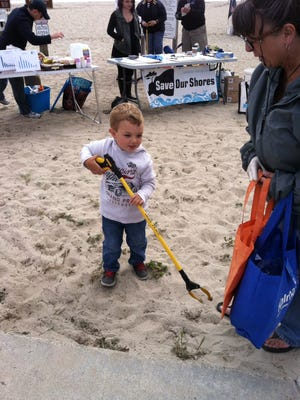 A young Save Our Shores volunteer tries out a trash grabber at Del Monte Beach in Monterey County during the annual Earth Day coastal cleanup.