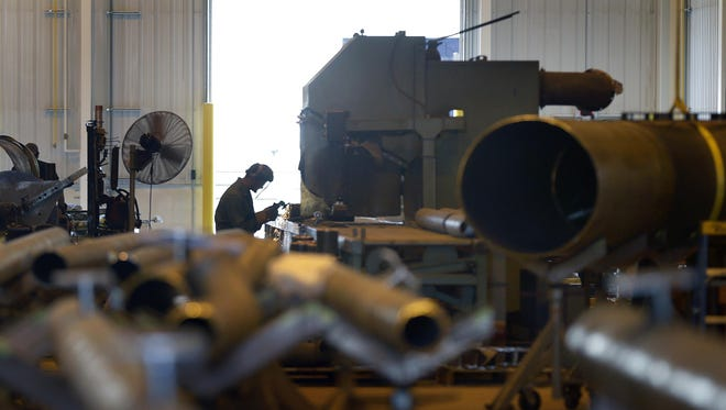 A worker uses a grinder at Team Industries in Kaukauna. The company is undergoing a multiphase expansion that has included hiring about 135 new employees since the year began.