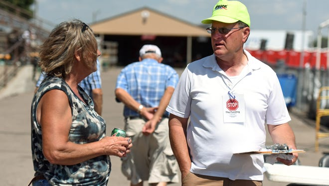 """Stop The Funding"" Co-Chair Bruce Danielson (right) talks with people and gathers signatures at the W.H. Lyon Fairgrounds during the Sioux Empire Fair recently"