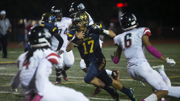 Naples quarterback Jordan Persad-Tirone, #17, carries the ball during their matchup against the South Fort Myers Wolfpack at Staver Field on Friday, Oct. 21, 2016 in Naples, Florida. The Wolfpack defeated the Eagles 42-35.