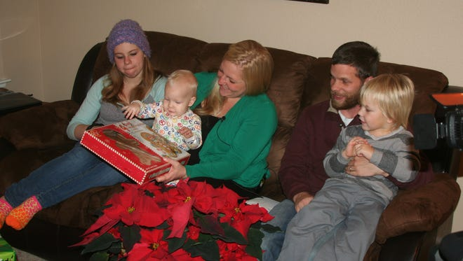 U.S. Army Cpl. Todd Lipscomb and his wife, Andrea, and children, Macie, Liam and Lucy, react after opening one of the presents given to them by Bank of America. The family recently moved into a home provided to them by the bank and the Military Warriors Support Foundation as part of its Homes 4 Wounded Heroes Program.
