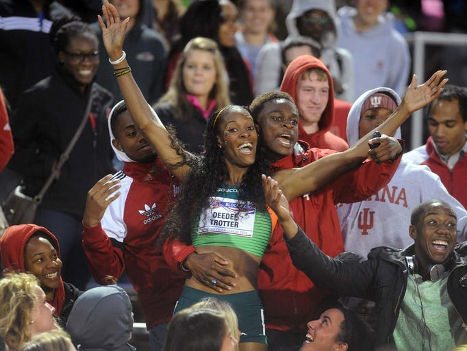 DeeDee Trotter celebrates with fans after winning the 400-meters. The American Track League debuted at the Indiana University track facility in Bloomington Friday May 2, 2014.