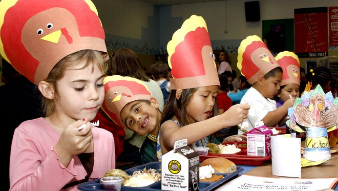 In 2011, Tombaugh Elementary School first-graders Kayle Emerson, 7, left, Brian Voelz, 6, Jemini Chitamin, 7, and Elias Romero, 6, gobble down their Thanksgiving Day lunch.