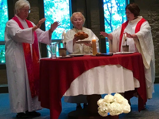 Abigail Eltzroth, right, prepares to celebrate communion