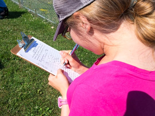 Air Quality Division environmental engineer Lauren Magirl records results of a reading Thursday, July 19, 2018, at the Port Huron Little League Park.