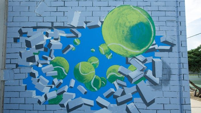 Teens in the Park and Recreation Department's Youth Mural Arts Program are working on a tennis-themed mural behind Laabs Pool.