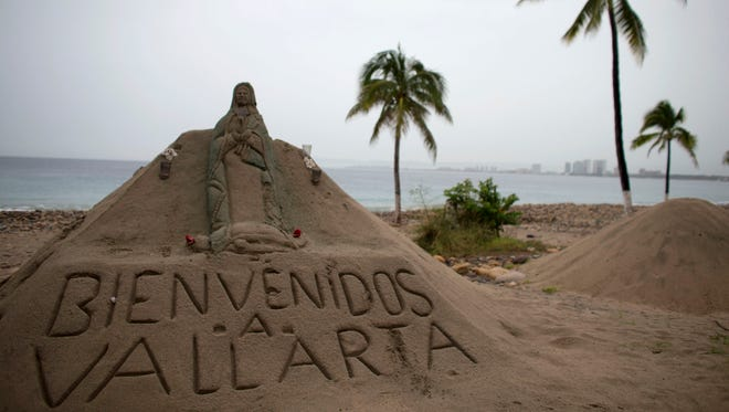 "A sand sculpture carved with a message that reads in Spanish; ""Welcome to Vallarta"" decorates the beach in Puerto Vallarta, Mexico."