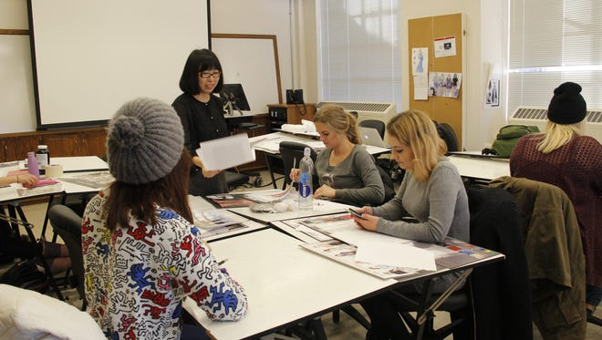 Ling Zhang (second from left) works with undergraduate Iowa State students Madeline Norris (left), Simona Labudyte (second from right) and Mhairi Galloway (far right) in the fashion illustration class she leads on Wednesday, Dec. 9.