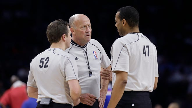 Referee David Jones, center, talks with referees Scott Twardoski (52) and Bennie Adams (47) during the second half of an NBA basketball game.