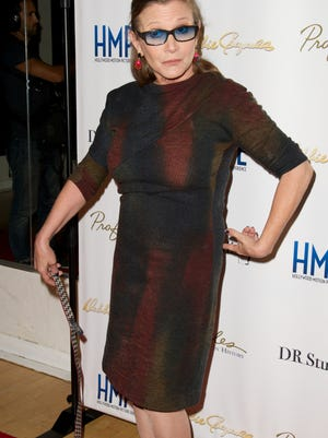 NORTH HOLLYWOOD, CA - MAY 14:  Actress Carrie Fisher poses at the press preview for the final Hollywood Motion Picture Collection Auction at Debbie Reynolds's Dance Studio on May 14, 2014 in North Hollywood, California.  (Photo by Earl Gibson III/WireImage) ORG XMIT: 491371341 ORIG FILE ID: 490769559