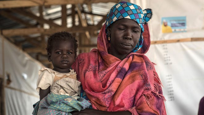 A woman holding her daughter leaves the International Rescue Committee health clinic in in Maiduguri in northeast Nigeria on July 7, 2017.