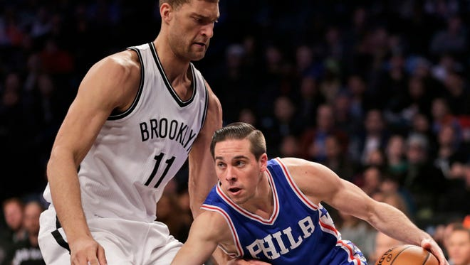 Philadelphia 76ers' T.J. McConnell, right, pushes past Nets' Brook Lopez during the Sunday's game at the Barclays Center.