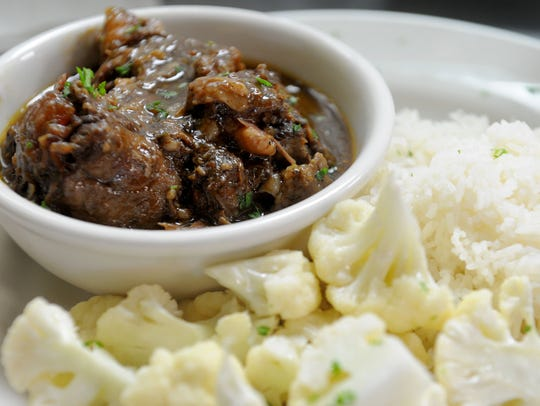Braised oxtail stew is served with rice and cauliflower