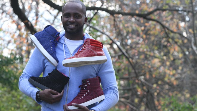 Allen Gabriel, a drug addiction counselor who has started his own line of shoes, Mascavii Footwear, poses with some of his shoes at his home in Neptune City.