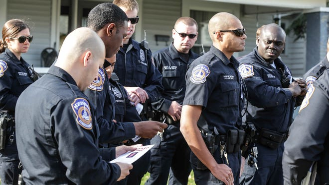 IMPD officers met for roll call Nov. 25, 2015, in the 3900 block of Graceland Avenue, where 10-year-old Deshaun Swanson was gunned down while attending a memorial service in September. Police were handed reward posters to post around the community looking for help to solve the case.