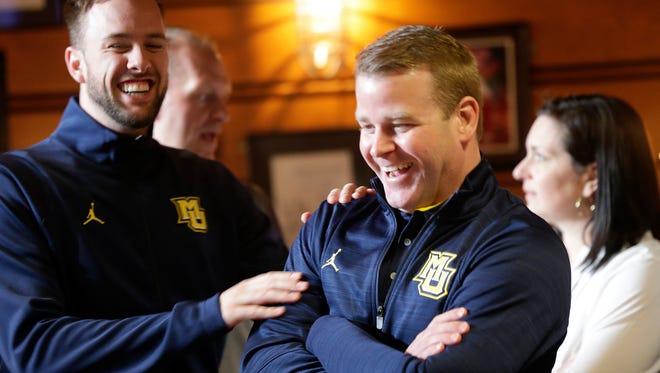 Marquette head coach Steve Wojciechowski (right) smiles as he celebrates with Golden Eagles guard Katin Reinhardt.