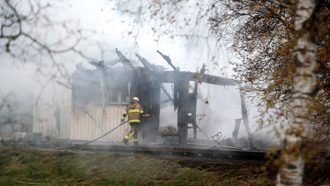 A Tuesday, Oct. 20, 2015 photo from files showing a firefighter working in the smoking remains of an accommodation home for asylum seekers near Munkedal in western Sweden. 14 people were safely evacuated from the conflagration that Swedish police were investigating as suspected arson.