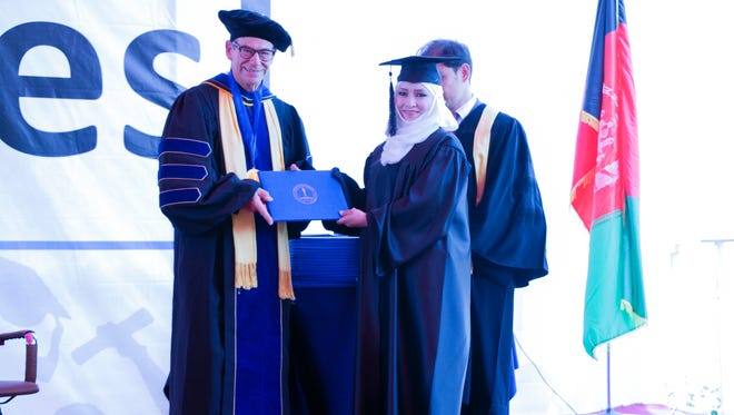 Ken Holland presents a diploma to a graduate of American University of Afghanistan.
