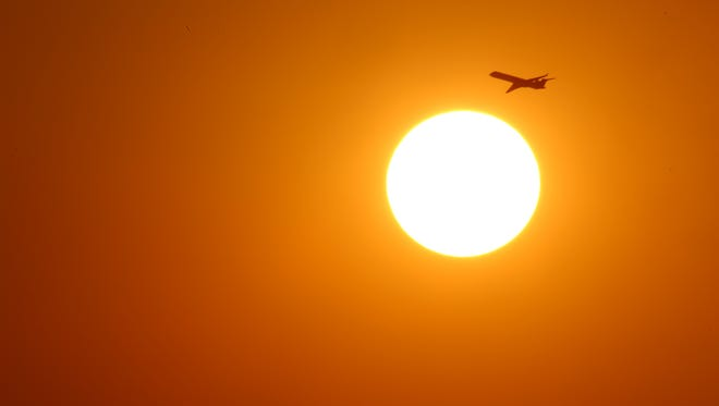 A jet takes-off from Sky Harbor international Airport and flies over the sun on the summer solstice on Jun. 21, 2017, in Phoenix.